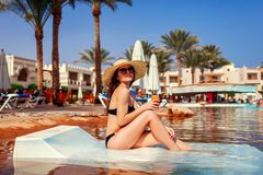 Woman relaxing in hotel swimming pool lying on chaise-longue with cocktail. Summer vacation. All inclusive. Woman in bikini relaxing in hotel swimming pool lying stock images