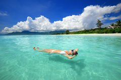 Woman in bikini relaxing lying on the water Royalty Free Stock Image