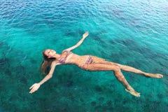 Woman in bikini relaxing lying on the water Royalty Free Stock Image