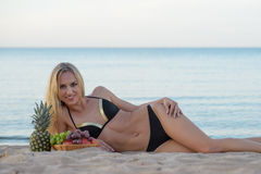 Woman in  bikini relaxing on the sand with fruits Stock Image