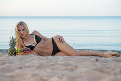 Woman in  bikini relaxing on the sand with fruits Royalty Free Stock Photography