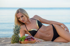 Woman in  bikini relaxing on the sand with fruits Stock Photo