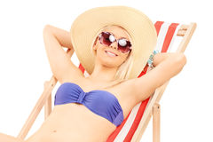 Woman in bikini relaxing on a sun lounger Stock Photo