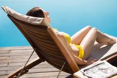 Woman in bikini relaxing by swimming pool Royalty Free Stock Photos