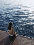 Woman In Bikini Relaxing On Yacht's Floorboard. Rear view of woman in bikini relaxing on yacht's floorboard while looking at ocean Royalty Free Stock Images