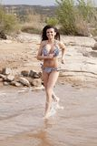 Woman in bikini running in water Stock Photos