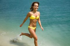 Woman in  bikini runs in water Stock Image
