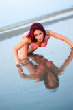 Woman in bikini at the sea, reflection on water. Red hair woman with amazing slim body wearing red bikini reflection on water as she lie at the sea lifting her Royalty Free Stock Photography