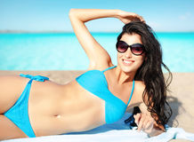 Woman in bikini and shades sunbathing on beach stock images
