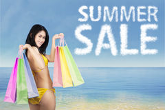 Woman with bikini and shopping bags at coast Royalty Free Stock Photo