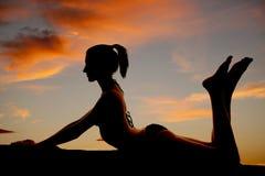 Woman bikini silhouette lay on stomach Stock Images