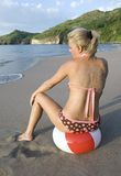 Woman in bikini sitting on beach ball on beach stock photography