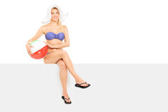 Woman in bikini sitting on a panel and holding a beach ball Royalty Free Stock Photos