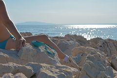 Woman in bikini sitting on the seashore and tanning her breasts and blue sky stock image