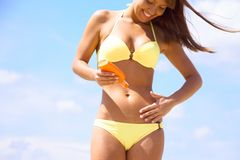Woman in bikini smear protective cream Stock Images