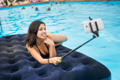 Woman in bikini smiling and taking selfie photo on the phone with selfie stick on a mattress in the pool at the resort. royalty free stock images
