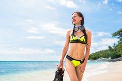 Woman in bikini with snorkelling gear walks on beach Royalty Free Stock Photos