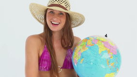 Woman in a bikini spinning a globe stock video footage