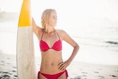Woman in bikini standing with a surfboard on the beach Royalty Free Stock Images
