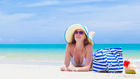 Woman in bikini and straw hat with beach bag and Stock Photography
