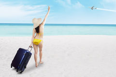 Woman in bikini with suitcase at beach Stock Image
