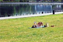 Woman in bikini sunbathing by the pond, lying on grass, reading paper book royalty free stock photo