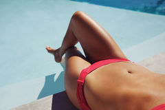 Woman in bikini sunbathing by the poolside Stock Photography