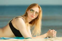 Woman in bikini sunbathing and relaxing on beach Royalty Free Stock Photography