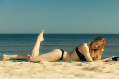Woman in bikini sunbathing and relaxing on beach Royalty Free Stock Photos