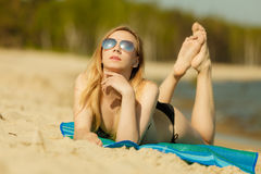 Woman in bikini sunbathing and relaxing on beach Royalty Free Stock Photography