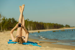 Woman in bikini sunbathing and relaxing on beach Stock Photo