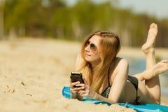 Woman in bikini sunbathing and relaxing on beach Stock Photo