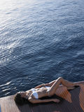 Woman In Bikini Sunbathing On Yacht's Floorboard Royalty Free Stock Photo