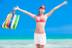 Woman in bikini and sunglasses with beach bag Royalty Free Stock Photo
