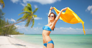 Woman in bikini and sunglasses over tropical beach. People, summer holidays and vacation concept - beautiful woman in bikini and sunglasses with pareo over Royalty Free Stock Photos