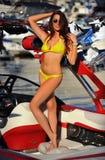 Woman in bikini and sunglasses posing pretty on motor speed-boat Stock Image