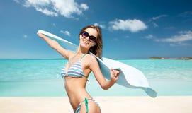 Woman in bikini and sunglasses with towel on beach Stock Photo