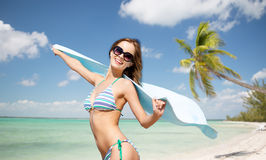 Woman in bikini and sunglasses with towel on beach Royalty Free Stock Photography