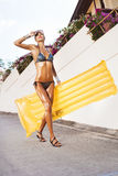 Woman in bikini in suntan oil with yellow float. Looking into the distance. Lifestyle, outdoors Stock Photo
