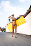 Woman in bikini in suntan oil with yellow float. Young woman in bikini in suntan oil with yellow float laughing and walking on the summer street. Lifestyle Stock Photography