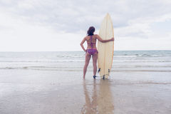 Woman in bikini with surfboard on beach Royalty Free Stock Image
