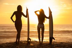 Woman Bikini Surfer Girls & Surfboards Sunset Beach. Rear view of two beautiful young women surfer girls in bikinis with white surfboards on a beach at sunset or royalty free stock photography