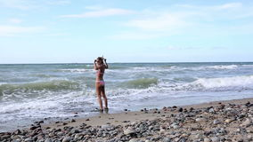 Woman in bikini with swimming goggles and flippers trying to get into the cold water stock footage