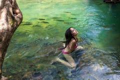 Woman with bikini swimming in the waterfall of Bon Royalty Free Stock Image