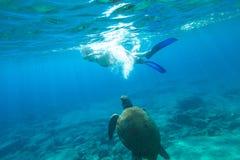 Snorkeler female sea turtle. Woman bikini swims encountering sea turtle Caretta in crystal waters of Foneas Beach, Mani peninsula, Greece. Watersport activity Royalty Free Stock Image