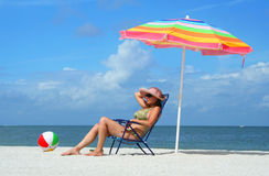 Woman in bikini tanning on the beach. A young woman in bikini tanning while sitting under a colorful umbrella on a beach. Travel & Vacation Collection Stock Photos