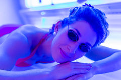 Woman in bikini tanning in wellness spa. Solarium stock photo