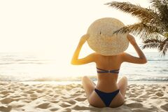 Free Woman Bikini Tropical Beach Back View. Beauty Model Girl In Sumer Hat Sun Tanning Under Palm. Summer Beach Vacation. Holiday Sea Royalty Free Stock Photo - 215355365