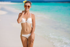 Woman in bikini at tropical beach. Beautiful young woman laying in the sea coast of Maldives. woman on tropical beach at resort with palm tree and bungalows Stock Images