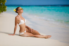 Woman in bikini at tropical beach. Beautiful young woman laying in the sea coast of Maldives. woman on tropical beach at resort with palm tree and bungalows Stock Photo